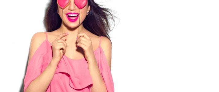 Image of a smiling woman with two love heart shaped lolly pops over her eyes